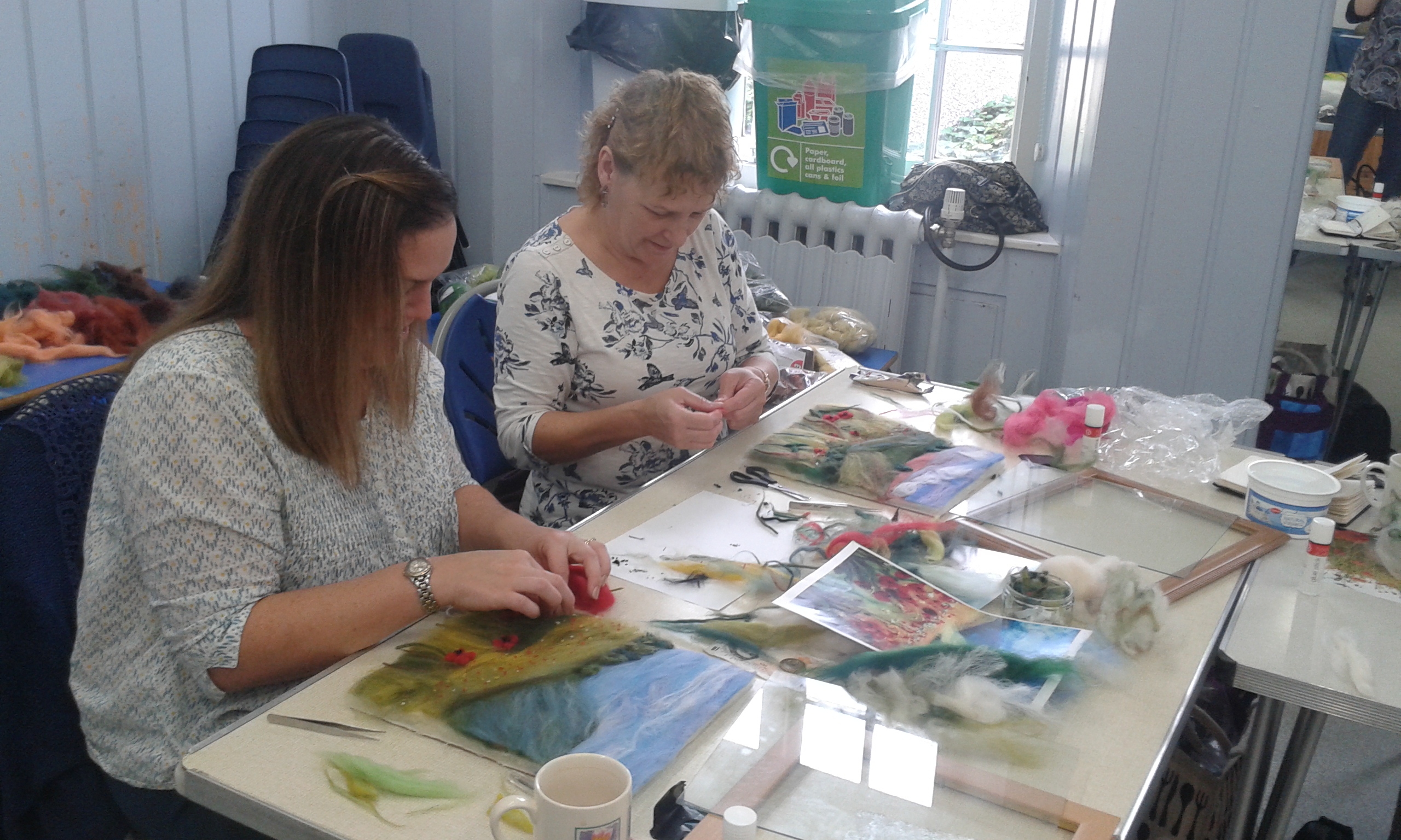 Friends Sally and Sally working on their wool painting landscapes.