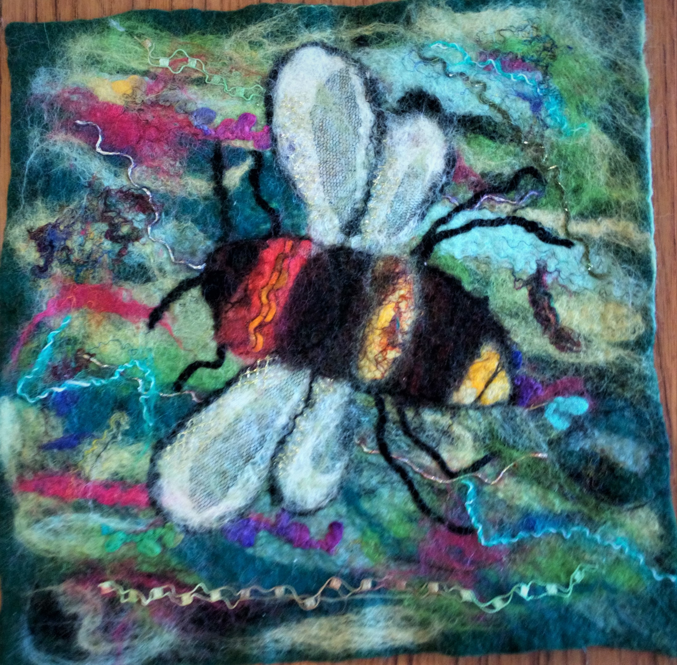 Wet Felted picture of the Bee decorated with various fibres, threads and silks.